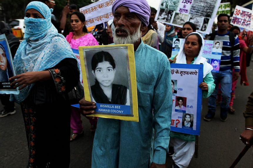 Indian Bhopal Gas disaster victim Barkat Ali (middle) holds a photograph of his daughter who was killed in the disaster during a commemoration rally in Bhopal on Dec 1, 2014.-- PHOTO: AFP
