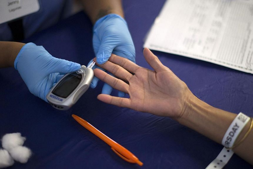 A visitor receiving a test for diabetes at the Care Harbor LA free medical clinic in Los Angeles, California, on Sept 11, 2014. Diabetes ages the mind about five years faster than normal. -- PHOTO: REUTERS