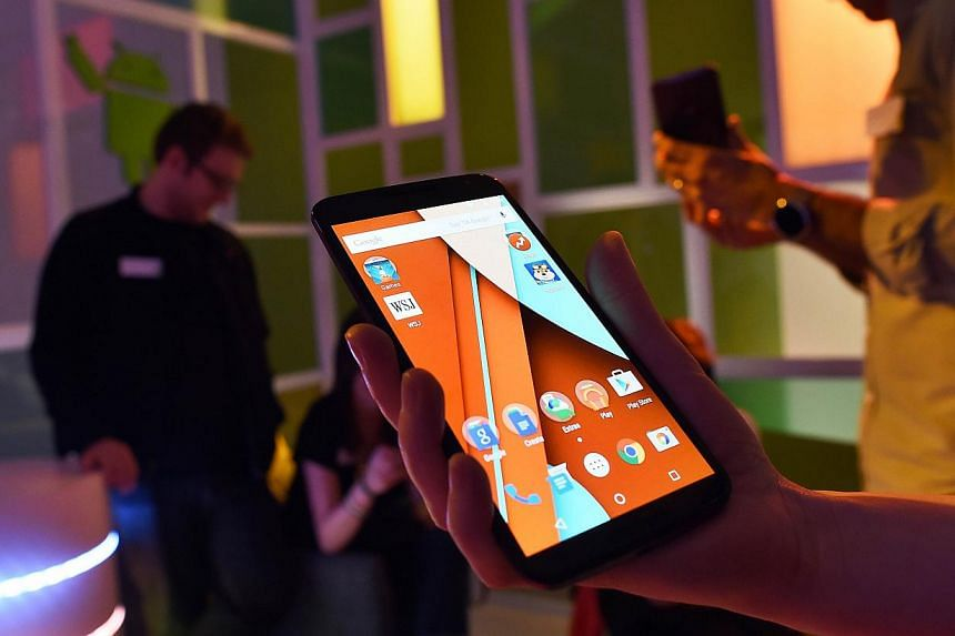 "Journalists look at Google's nexus 6 smartphone during a media preview in New York on Oct 29, 2014. The global smartphone market will see cooler growth in the next few years, amid ""cutthroat"" competition that will bring down prices for many consumers"