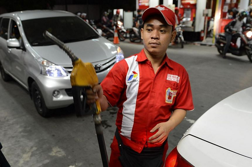 In this Nov 17, 2014 photo, a fuel attendent at a state-owned Pertamina fuel station prepares to fill up motorists vehicles in Jakarta. Indonesia's new administration plans a major expansion of oil storage and will construct more refineries as part o