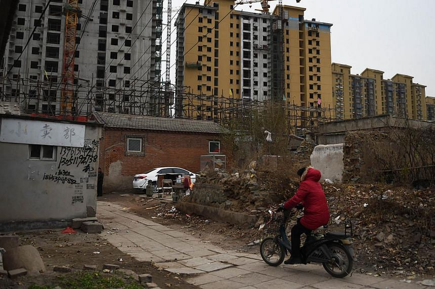 A woman rides past rows of newly built apartments in Beijing on Nov 27, 2014. China will implement long-awaited property registration rules from March, in a move that could give the country's anti-corruption investigators extra ammunition and pave th