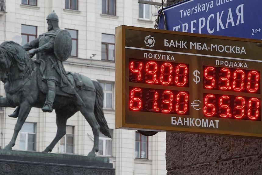 A board showing currency exchange rates, in front of a monument to Prince Yury Dolgoruky who founded Moscow in 1147, in the capital Moscow, on Dec 1, 2014. -- PHOTO: REUTERS