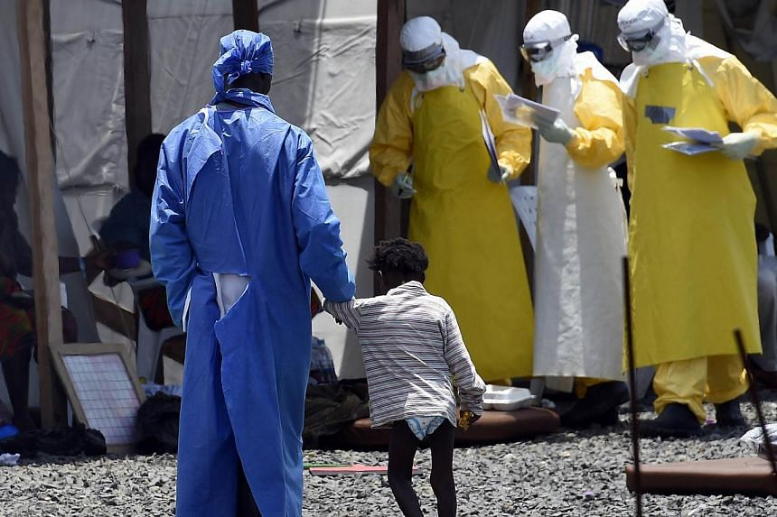 A nurse walks with a little girl suffering from Ebola, at the international medical NGO Medecins Sans Frontieres (MSF) in Monrovia on Sept 27, 2014.The World Health Organisation on Monday said more than 6,000 people had died from Ebola and not nearly