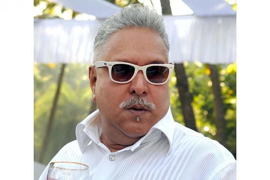 In this photograph taken on Dec 21, 2013, Indian United Breweries Group chairman Vijay Mallya attends the launch of the Kingfisher 2014 calendar in Mumbai. -- PHOTO: AFP