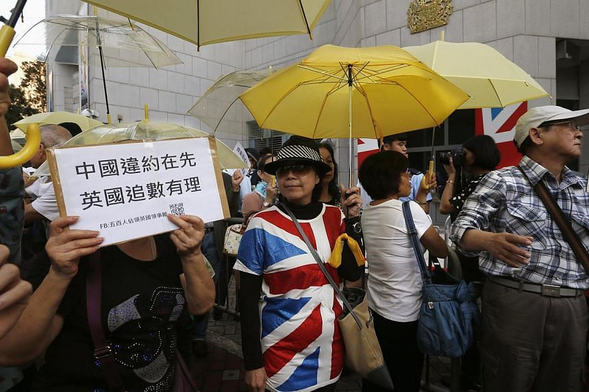 "Pro-democracy protesters carrying yellow umbrellas, a symbol of the Occupy Central civil disobedience movement, demonstrate outside the British Consulate in Hong Kong on Nov 21, 2014. China rebuffed as ""useless"" on Tuesday complaints from Britis"