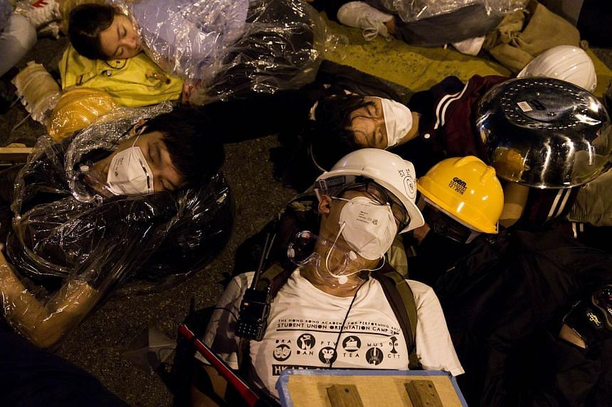 Pro-democracy protesters rest after clashes with police on an occupied road near the government headquarters in the Admiralty district of Hong Kong early on Dec 1, 2014.Hong Kong's pro-democracy occupation is entering its death throes with radi