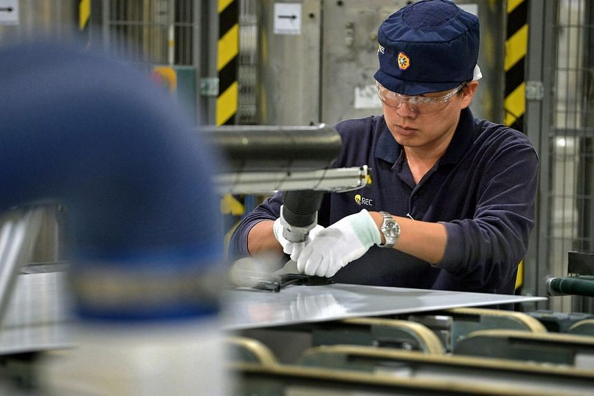 An employee works on solar panels on the module production line at the REC Solar ASA manufacturing facility at Tuas on Sept 5, 2014.The manufacturing sector's hopes for a festive season boost are likely to end in disappointment going by data ou