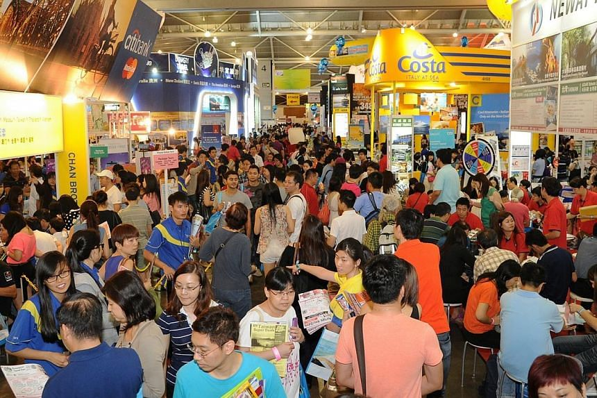 Visitors thronging the various booths during a National Association of Travel Agents Singapore (Natas) Travel Fair held at the Singapore Expo. The association said it would be bringing forward its fair next year to March 6-8.-- PHOTO: NATAS