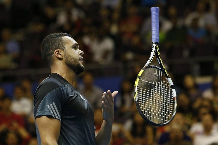 Manila Mavericks' Jo-Wilfried Tsonga of France tosses his racquet in frustration during his men's singles match against Singapore Slammers' Tomas Berdych of the Czech Republic at the International Premier Tennis League (IPTL) in Singapore Dec 2, 2014