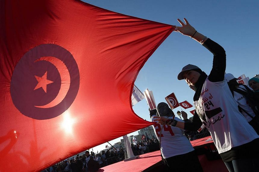 A supporter of Moncef Marzouki, the current Tunisian president who is defending his position in the upcoming presidential elections holds up her national flag during a campaign rally on Nov 19, 2014, in Bizerte, north-east of Tunis. Tunisia's ne