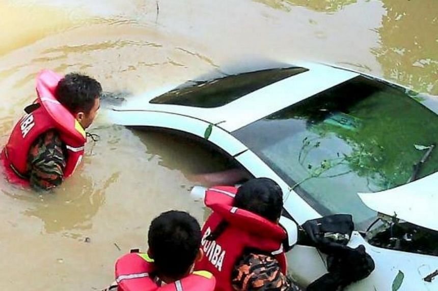 A fire and rescue team at the scene of an accident where a sports car veered off the road and plunged into a river. The driver was found dead at the scene. -- PHOTO: THE STAR/ASIA NEWS NETWORK