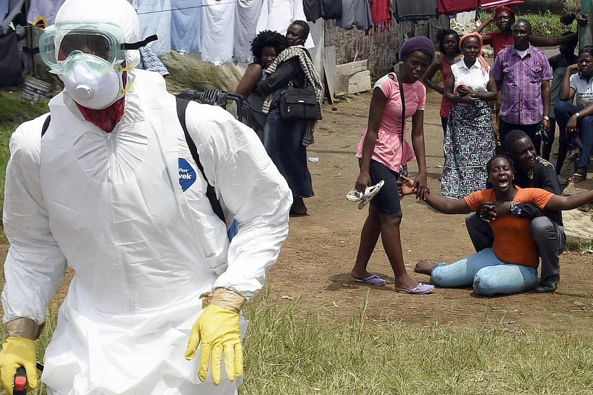 People look on as a woman reacts after her husband is suspected of dying from the Ebola virus, in the Liberian capital Monrovia on Oct 4, 2014. -- PHOTO: AFP