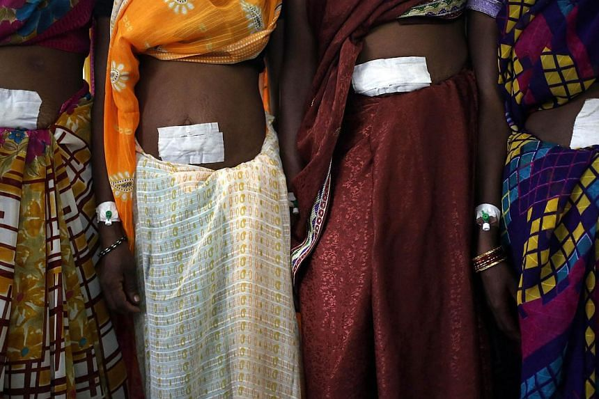 Women, who underwent sterilisation surgery at a government mass sterilisation camp, pose for pictures inside a hospital at Bilaspur district in the eastern Indian state of Chhattisgarh in this Nov 14, 2014 file photo. -- PHOTO: REUTERS