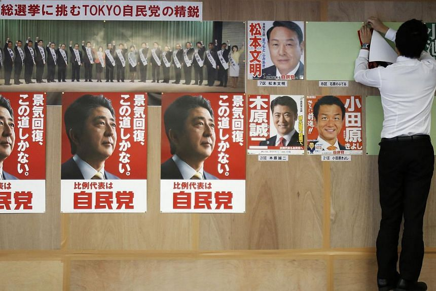 A staff member of Japan's ruling Liberal Democratic Party (LDP) puts up posters of election candidates on a wall at the LDP regional election office in Tokyo on Dec 2, 2014. -- PHOTO: REUTERS