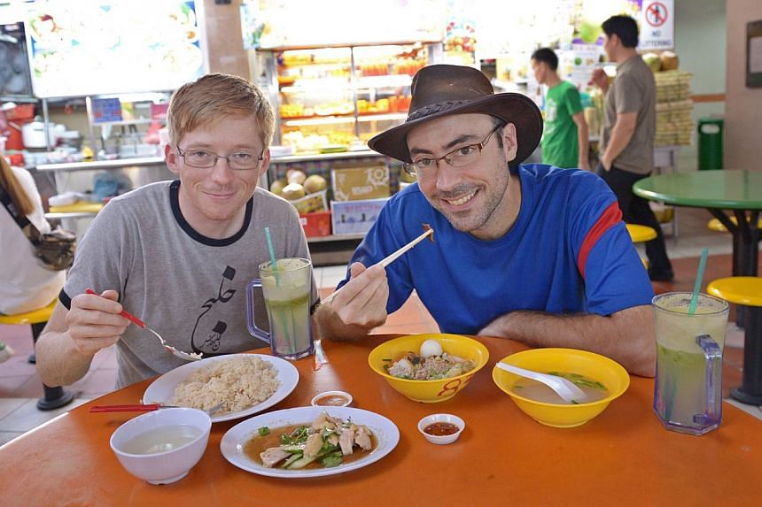 Two French men, Killian Blais (with hat), 31 and William Kohler, 31, tucking in local food at Maxwell Road Food Centre on Dec 1, 2014. -- ST PHOTO: LIM SIN THAI