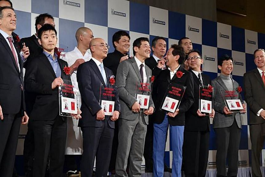 The heads of three-star restaurants selected by the new Michelin Guide Tokyo 2015 guidebook pose at a photo session during the publication announcement ceremony in Tokyo on Dec 02, 2014, along with Michelin Japan president Bernard Delmas (left) and M