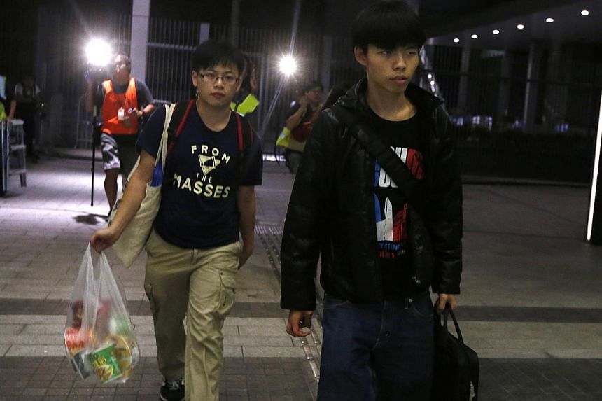 Student leader Joshua Wong (right) walks with a fellow student carrying cup noodles into the Legislative Council in Hong Kong on Sunday. Speaking on a stage on Monday night in the heart of the Admiralty protest site next to government headquarters, W