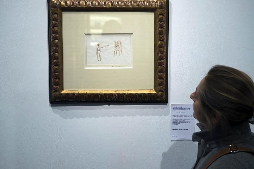 A woman in Paris looks at a watercolour from Antoine de Saint-Exupery showing the Turkish astronomer who discover the planet of The Little Prince. The painting valued between 400 000 and 500 000 euros will be auctioned next December 9. -- PHOTO: AFP
