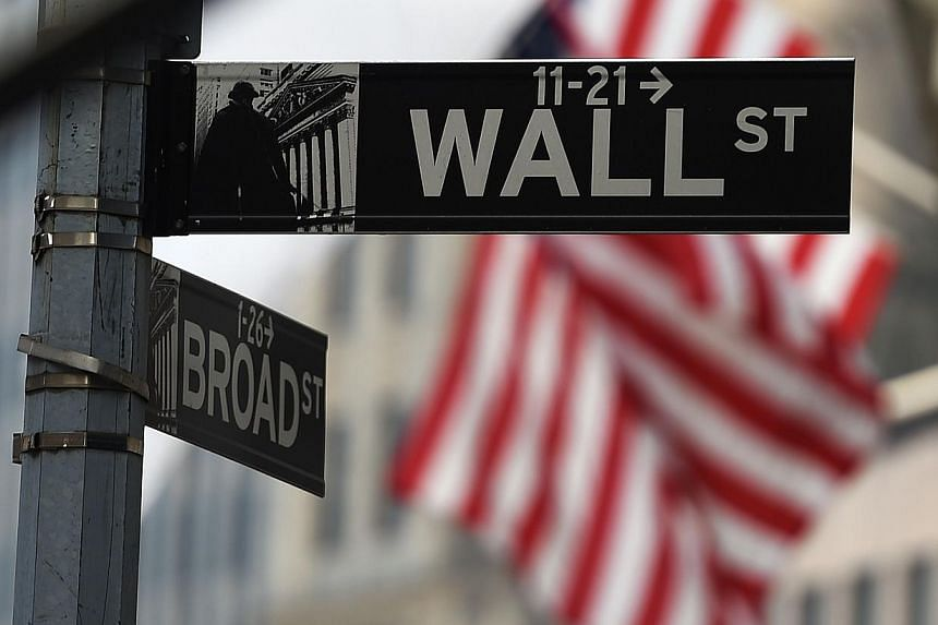 """A Wall Street sign near the New York Stock Exchange (NYSE) building in New York. Wall Street stocks opened higher on Tuesday after stores reported their bigges ever """"Cyber Monday"""" sales. -- PHOTO: AFP."""