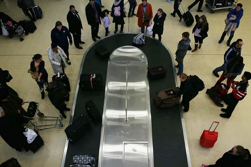 Travellers wait for their luggage after arriving at Ronald Reagan Washington National Airport on Nov 26, 2014. A doctor who cracked a joke about a bomb in his luggage partly forced the evacuation of Miami International airport on Oct 22, and earned a