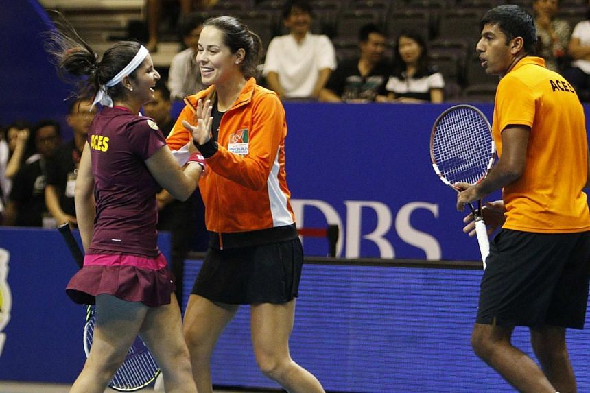 Team Micromax Indian Aces' Ana Ivanovic (centre) of Serbia celebrates with teammates Sania Mirza (left) and Rohan Bopanna of India after their mixed doubles match against UAE Royals at the International Premier Tennis League (IPTL) in Singapore on De