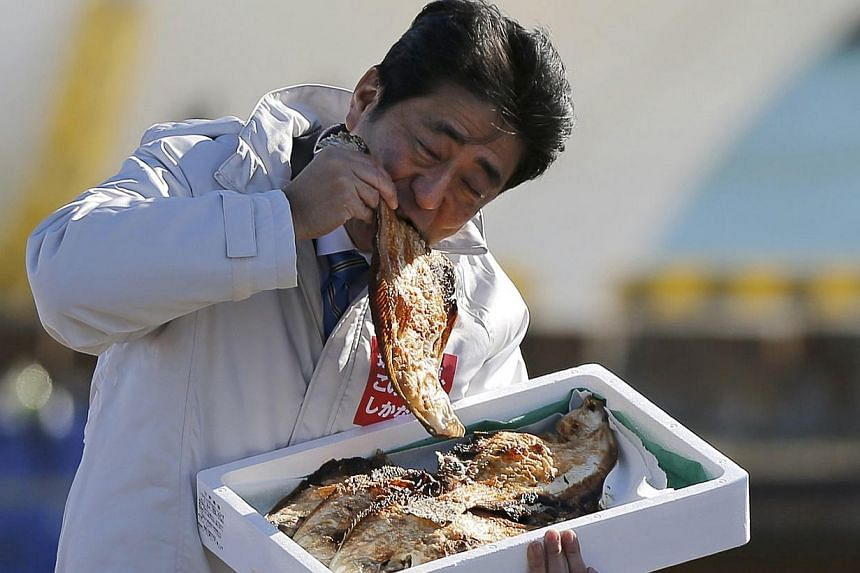 Japan´s Prime Minister Shinzo Abe, who is also leader of the ruling Liberal Democratic Party (LDP), eats a local grilled fish during his official campaign kick-off for the Dec 14 lower house election, at the Soma Haragama fishing port in Soma, Fukus