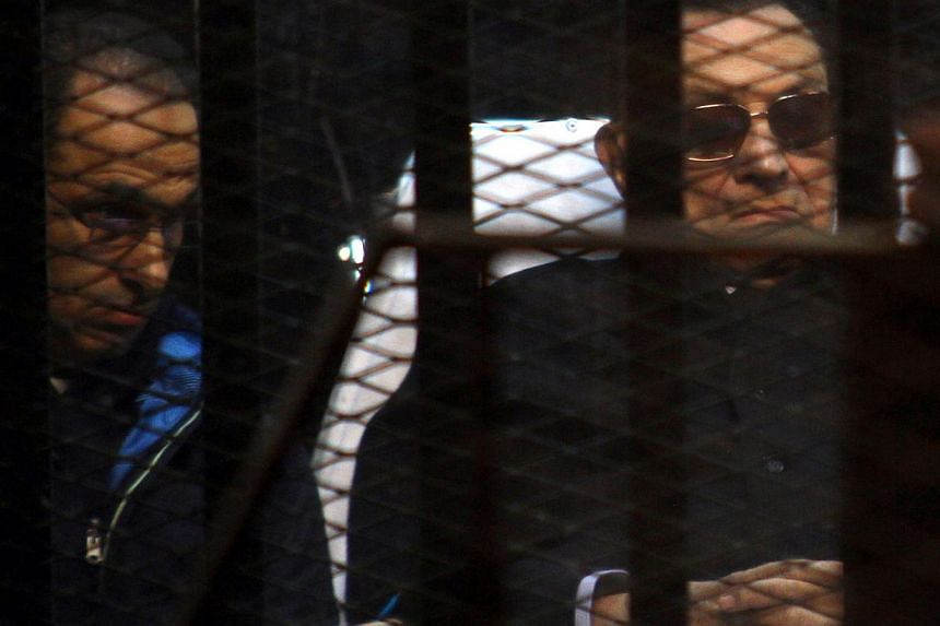 Egypt's former president Hosni Mubarak (right) and his son Gamal sit behind bars during a court hearing on Nov 29, 2014 in the capital Cairo. Egypt's public prosecutor appealed on Tuesday against a court decision last Friday to drop charges against M