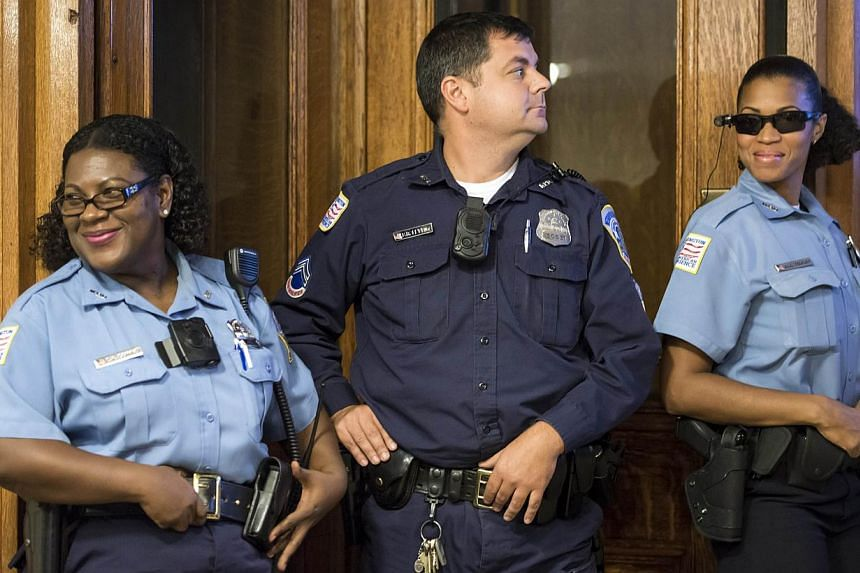 Modelling body cameras are (from left) Washington DC Police Officer Debra Domino, Master Patrol Officer Benjamin Fettering and Officer JaShawn Colkley at a press conference at City Hall on Sept 24, 2014 in Washington, DC. The Washington Metropolitan