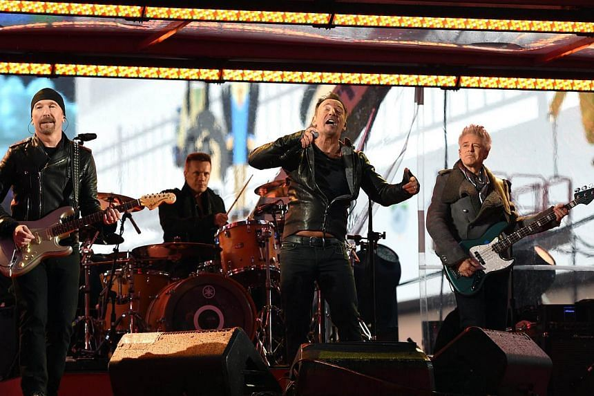 Bruce Springsteen performs along with The Edge and Larry Mullen Jr. and Adam Clayton of U2 during the World AIDS Day (RED) concert in Times Square in New York on Dec 1, 2014. -- PHOTO: AFP