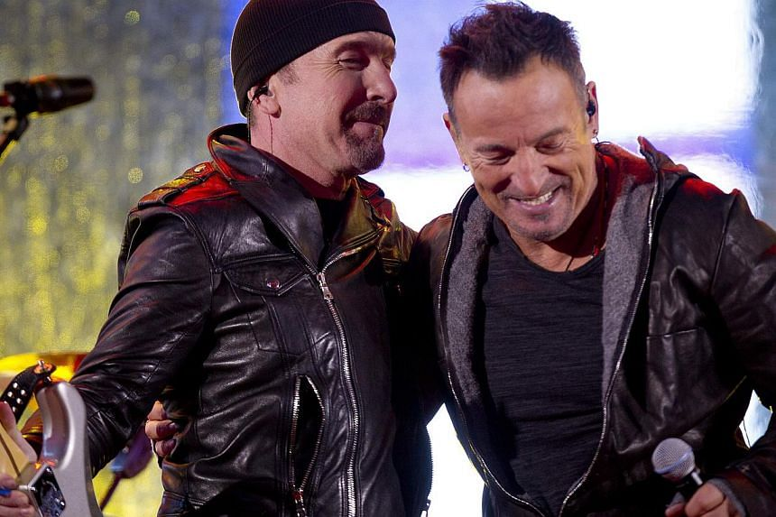 The Edge and Bruce Springsteen (right) perform during a surprise concert in support of World AIDS Day in Times Square in New York on Dec 1, 2014. Springsteen filled in for U2's injured lead singer Bono on Monday evening. -- PHOTO: REUTERS