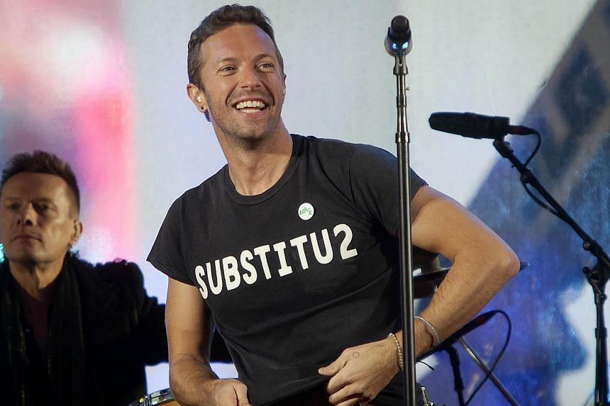 """Chris Martin wears a shirt that says """"SUBSTITU2"""" as he performs, in place of Bono, with U2 during a surprise concert in support of World AIDS Day in Times Square in New York on Dec 1, 2014. -- PHOTO: REUTERS"""
