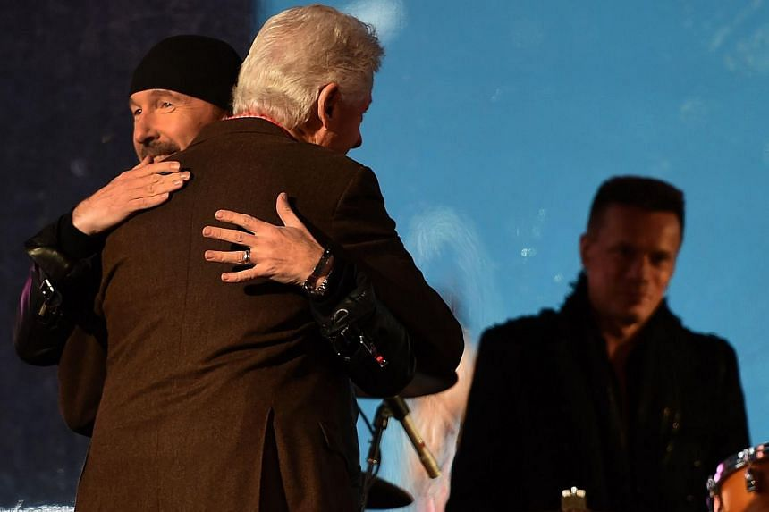 The Edge of U2 (left) hugs Former US president Bill Clinton during the World AIDS Day (RED) concert in Times Square in New York on Dec 1, 2014. -- PHOTO:AFP