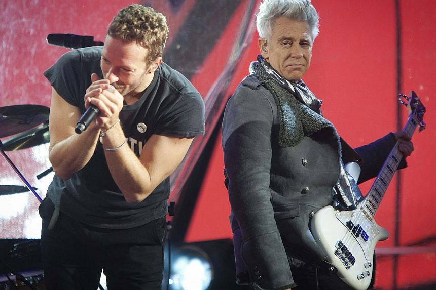 Chris Martin (L) and Adam Clayton perform during a surprise concert in support of World AIDS Day in Times Square in New York on Dec 1, 2014. -- PHOTO: REUTERS