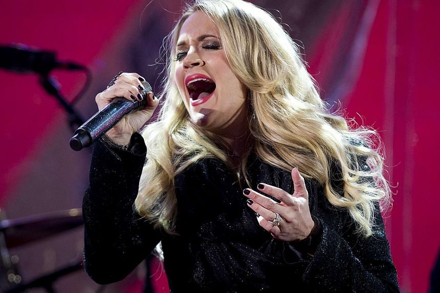 Carrie Underwood performs with U2 during a surprise concert in support of World AIDS Day in Times Square in New York on Dec 1, 2014. -- PHOTO:REUTERS
