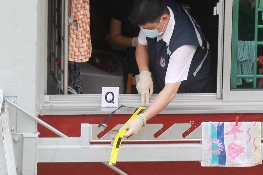 A police investigator at the kitchen window of the sixth-floor unit at Block 105 in Ang Mo Kio Avenue 4 where the dismembered body of Andrea Tay Su Lin was found at the foot of the same block on the morning of June 4, 2014. -- PHOTO: SHIN MIN