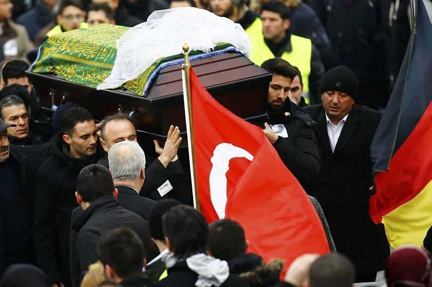 People carry a coffin holding the body of late student Tugce Albayrak during a memorial service in Waechtersbach, on Dec 3, 2014. Germans flocked to the funeral on Wednesday of a young woman of Turkish origin who has become a symbol of civic cou