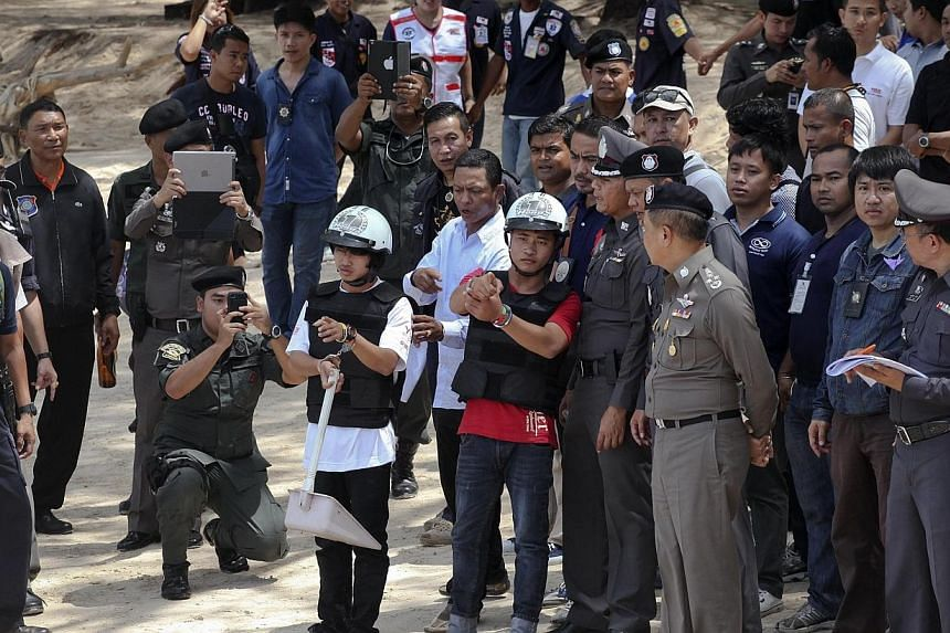 Two workers from Myanmar (wearing helmets and handcuffs), suspected of killing two British tourists on the island of Koh Tao last month, stand near Thai police officers during a re-enactment of the alleged crime on Oct 3, 2014.Thai prosecutors