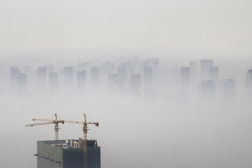 A building under construction is seen amid smog on a polluted day in Shenyang, Liaoning province, on Nov 21, 2014. -- PHOTO: REUTERS