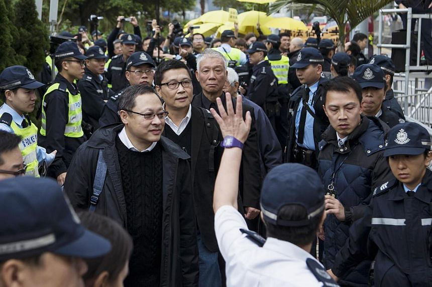 (Left to right) Occupy Central civil disobedience founders Benny Tai, a law professor at the University of Hong Kong, Chan Kin-man, a professor of sociology at Chinese University, and Reverend Chu Yiu-ming walk to Central police station in Hong Kong