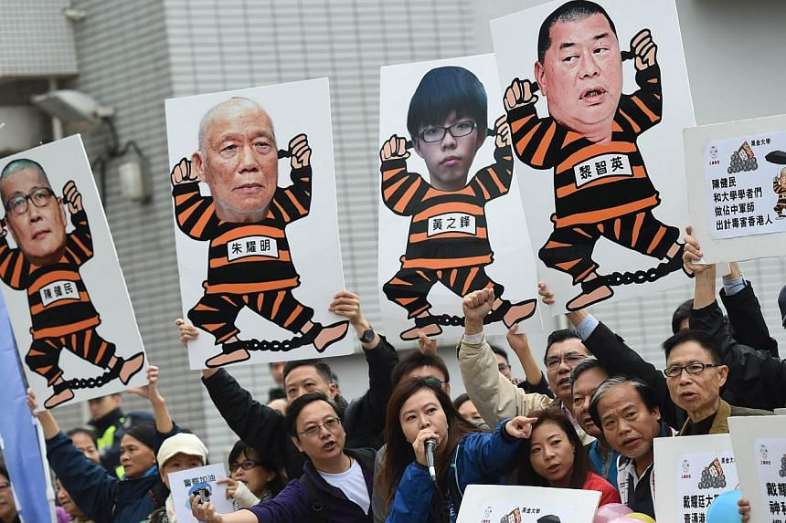 Anti Occupy Central movement protesters hold placards and shout slogans as the movement founders Benny Tai, Chan Kin-man and Chu Yiu-ming (not seen) prepare to surrender to police in Hong Kong on Dec 3, 2014. -- PHOTO: AFP