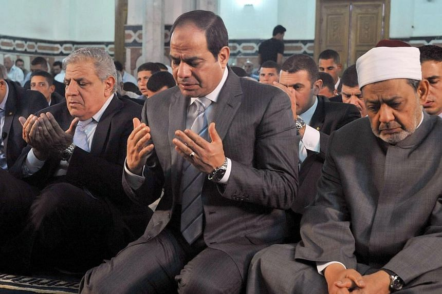 Egypt's President Abdel Fattah al-Sisi (centre), along with Grand Imam of al-Azhar Shiekh Ahmed el-Tayeb (right) and Prime Minister Ibrahim Mahlab (left) performing prayers on the Muslim holiday of Eid al-Adha, or feast of sacrifice, in the capital C