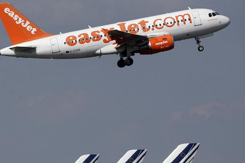 An easyJet aircraft takes-off past Air France plane tails at the Charles-de-Gaulle airport, near Paris, Sept 16, 2014. British finance minister George Osborne said he would scrap a tax charged on children flying out of the country, making it cheaper