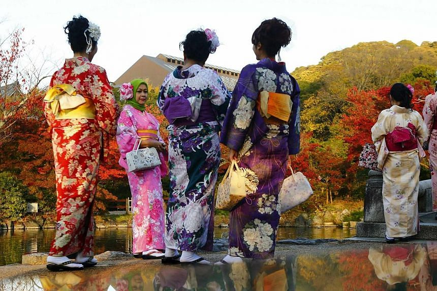 Tourists, dressed in traditional Japanese kimonos, stand in a park in Kyoto, western Japan on Nov 19, 2014.-- PHOTO: REUTERS