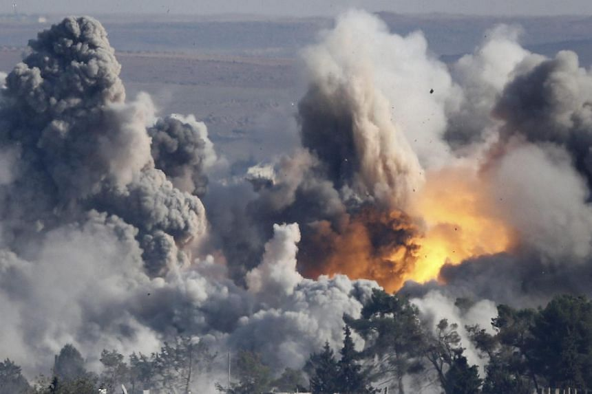 Smoke rises over Syrian town of Kobane after an airstrike on Oct 18, 2014, part of an offensive by a US-led coalition against the Islamic State in Iraq and Syria (ISIS).The coalition has inflicted serious damage on ISIS, carrying out around 1,0