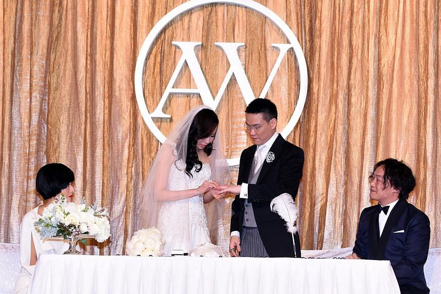 William So and Anita Fung exchange rings, with their matchmakers, Eason Chan and his wife Hilary Tsui, as their witnesses. -- PHOTO: APPLE DAILY