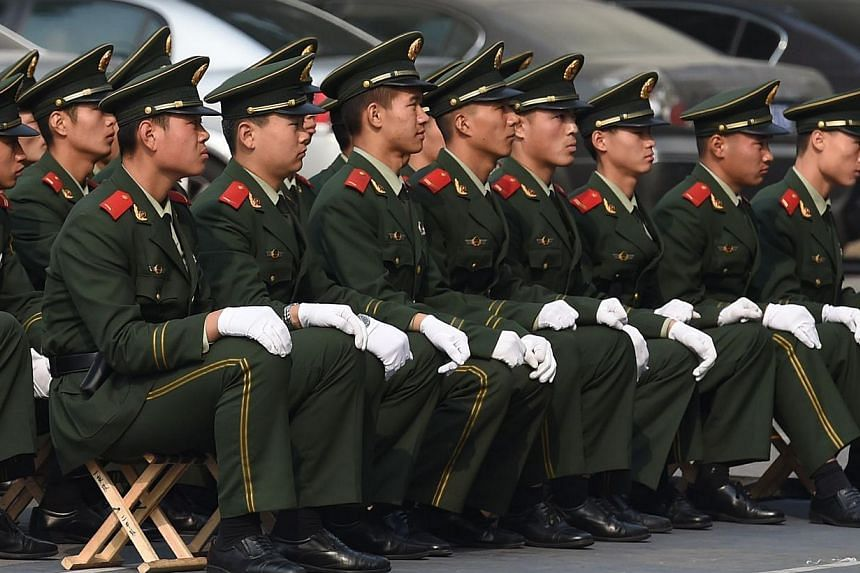 Chinese paramilitary policemen listen to a lecture outside their barracks in Beijing on Oct 29, 2014. China is to set up a database to trace corrupt officials who have fled overseas, the authorities have announced. -- PHOTO: AFP