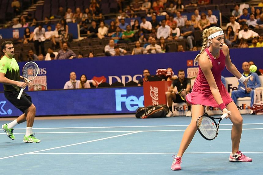France's Kristina Mladenovic (right) and Serbian Nenad Zimonjic (left) of the UAE Royals play against Belgium's Kirsten Flipkens and Canadian Daniel Nestor of the Manila Mavericks during their mixed doubles at the International Premier Tennis League