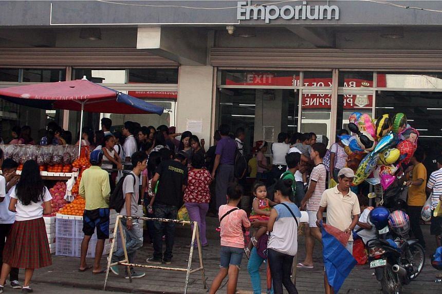 Residents crowd the entrance of a grocery store in Tacloban City, central Philippines on Dec 3, 2014, ahead of the landfall of Typhoon Hagupit. The Philippine government on Wednesday sent food and medical supplies to central provinces on the pat