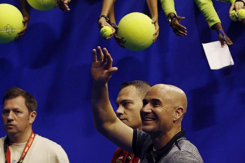 Singapore Slammers' Andre Agassi of the US waves to fans after the matches against Manila Mavericks at the International Premier Tennis League in Singapore Dec 2, 2014. American legend Agassi said the IPTL should take a lasting place in the sport des