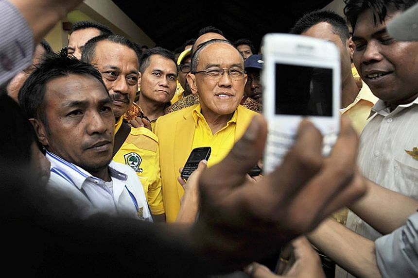 Aburizal Bakrie (centre), head of Indonesia's Golkar Party walks as he leaves the 9th Golkar Party National Conference in Nusa Dua, Bali resort island, Indonesia on Dec 1, 2014.Indonesia's second biggest party on Wednesday re-elected tycoon Abu